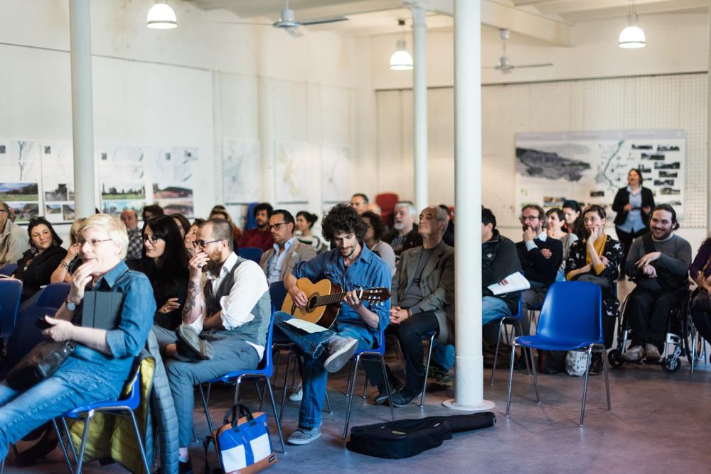 Jacopo Belli, seduto tra il pubblico, inizia a suonare con la sua chitarra la canzone che ha scritto sul Bisenzio
