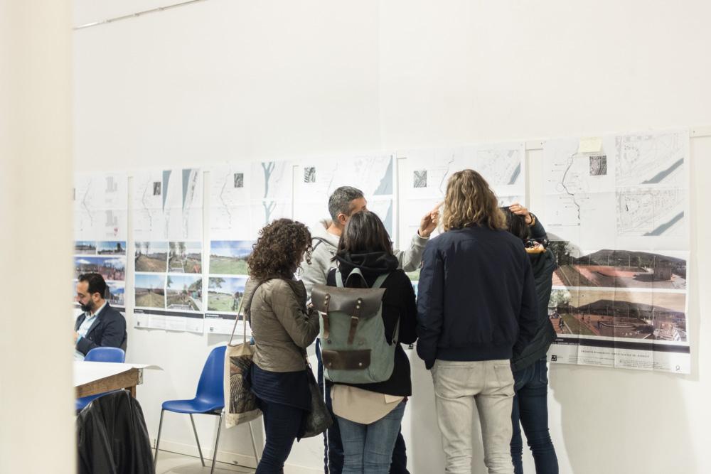Un gruppo di partecipanti discute sul progetto vicino ai rendering appesi alla parete